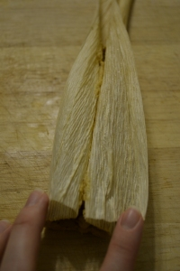 Press masa sides together over filling and wrap husk around.